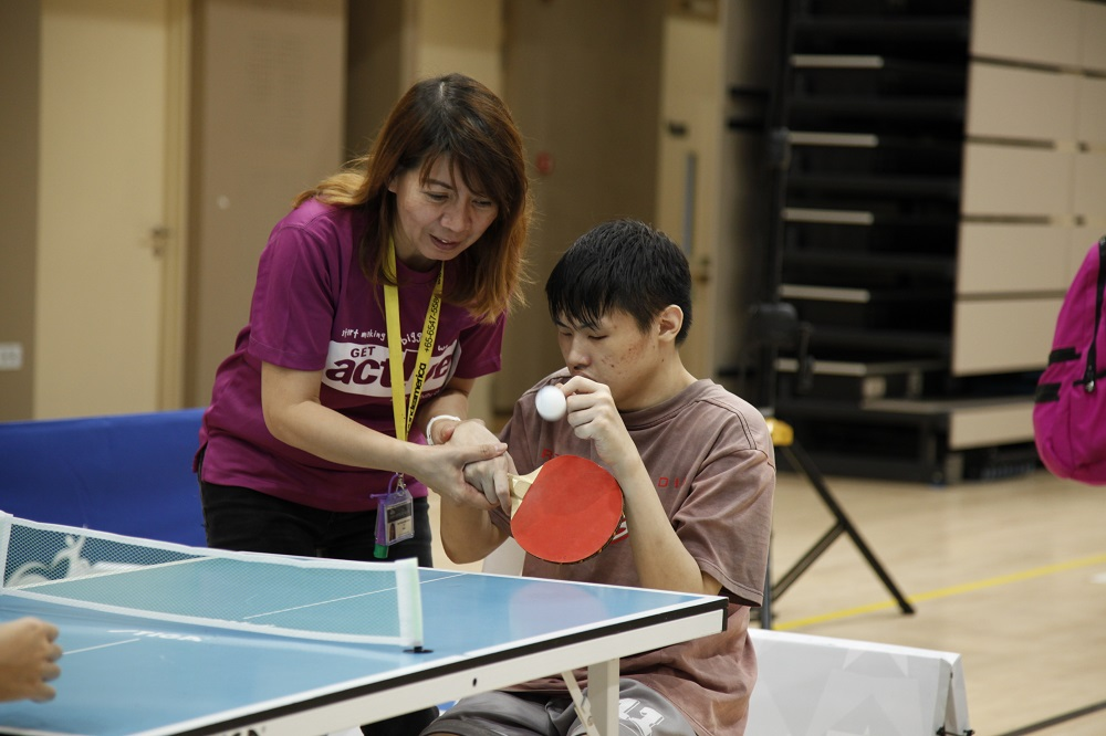 Team Nila volunteer assisting a member of the public to play table tennis during the launch of Inclusive Sports Festival. Photo by SportSG