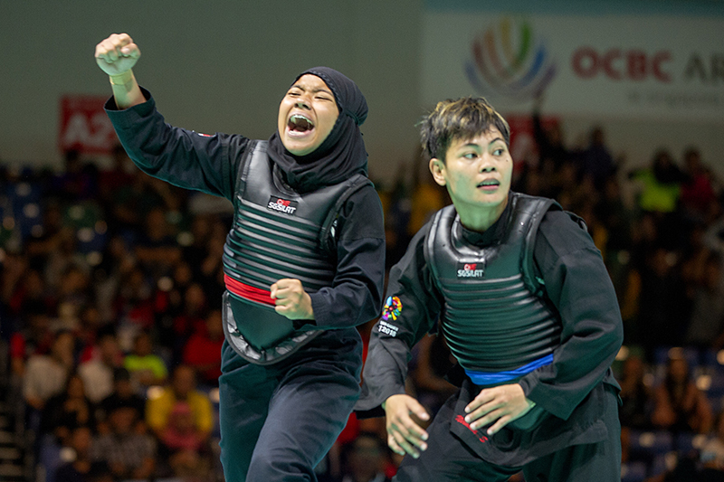 2018 World Pencak Silat Championship - Tanding - Female Category B, above 50-55kg - Semi Finals -  Singapore Sports Hub, OCBC Arena, Singapore - December 15, 2018 - Nur Syaza Inysirah Binte Md Roslan (SGP) celebrates after winning against Nirmalasari Octaviani (INA) Photo by Alfie Lee/SportSG