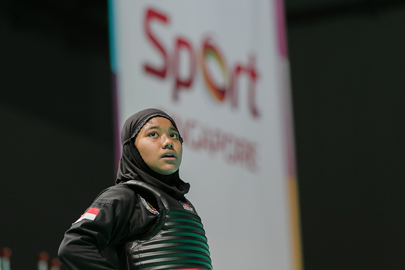 2018 World Pencak Silat Championship - Tanding - Female Category B, above 50-55kg - Semi Finals -  Singapore Sports Hub, OCBC Arena, Singapore - December 15, 2018 - Nur Syaza Inysirah Binte Md Roslan (SGP) v. Nirmalasari Octaviani (INA) - Nur Syaza Insyirah looked to the screen for the video replay after Indonesia protest. However, the decision was on Singapore side and won the match 3-2. Photo by Abdul Rahman/SportSG