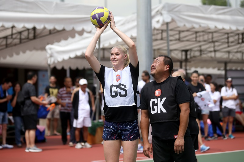 Jo Weston, Australian Diamonds attempting a goal while Alex Tan, Chief Innovation Officer, M1 looks on at the charity exhibition match at the M1 Corporate Netball Challenge on 10th November 2018. Photo: netball singapore