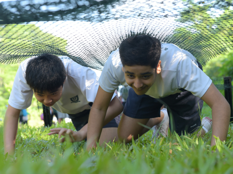 Two students from Broadrick Sec race against one another in a leopard crawl competition [Credit to AC Leong]